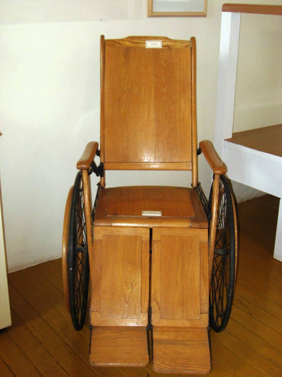 """WoodWheelchair"" by Thelmadatter - Own work. Licensed under Public Domain via Wikimedia Commons - http://commons.wikimedia.org/wiki/File:WoodWheelchair.JPG#mediaviewer/File:WoodWheelchair.JPG"